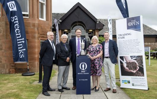 Martin Rhodes (the Scottish Fair Trade Forum) and Angus Coull (Bala Sport) alongside David and Val Gwynne from Troon Fairtrade Initiative, stand with Johnnie Cole-Hamilton, The R&A's Executive Director of Championships, and the Claret Jug beside a banner describing how The Open is using Fairtrade products in Troon.
