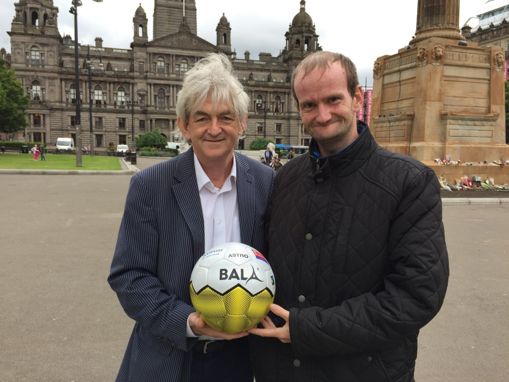 Homeless World Cup Founder Mel Young meets an event volunteer at the venue for the 2016 event, George Square in Glasgow.